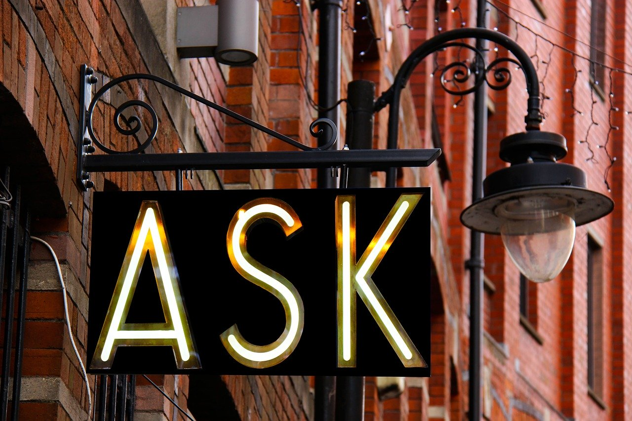 """Storefront sign that says """"ASK"""" in front of lamp and red building walls"""